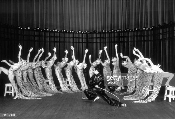 A scene from the show 'Round About Regent Street' with a ringmaster training a group of leopard women