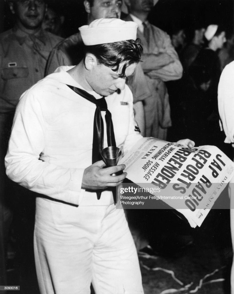 A sailor reading the news of the Japanese surrender in New York's Times Square in the early hours of tuesday morning. (Photo by Weegee(Arthur Fellig)/International Center of Photography/Getty Images)