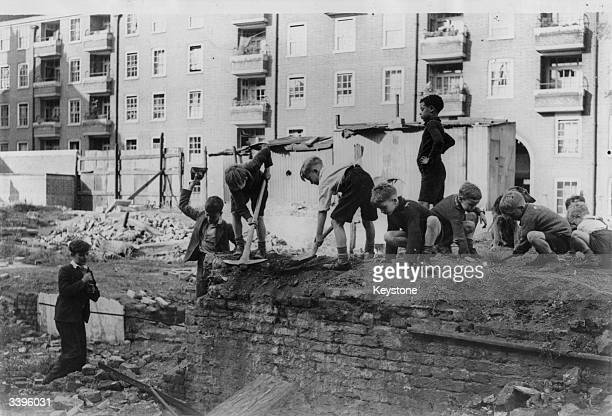 Boys clearing rubble on the bombed site of the Hopskotch Inn near Euston station London The site is to be turned into a junior club for children by...