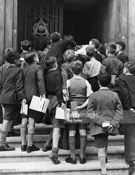 Group of enthusiastic Arsenal supporters gather at the main gate of Arsenal Football Stadium, waiting to collect autographs of the team after...
