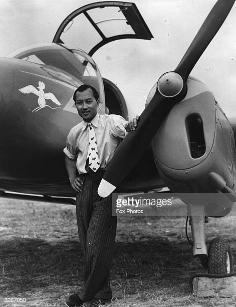Prince Birabongse of Thailand tries his hand at flying Here he poses beside his new Miles Gemini plane carrying his racing car emblem of a white mouse