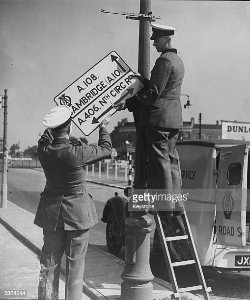 Two Automobile Association men putting up a signpost at the intersection of the Cambridge and North Circular roads to help relieve traffic congestion...