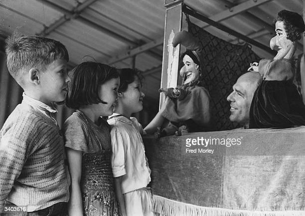 John Thelwell Kathleen Lacey and Evelyn Cleary being entertained by Punch and Judy at the Kensington Memorial Recreation Ground London