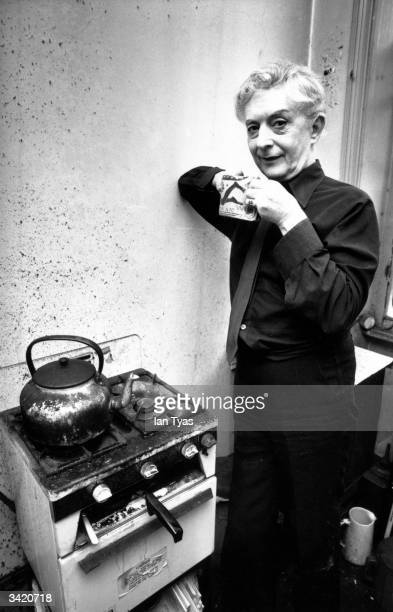 Quentin Crisp , at home in Chelsea, London, making a cup of tea with a kettle and stove he has been using for 37 years.
