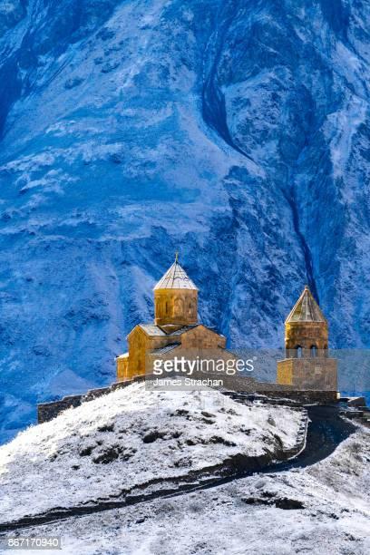 14th Century Tsminda Sameba Church, (Holy Trinity Church), Gergeti, at 2200m above Kazbegi, in dawn light against frozen Mount Kazbek, Georgia