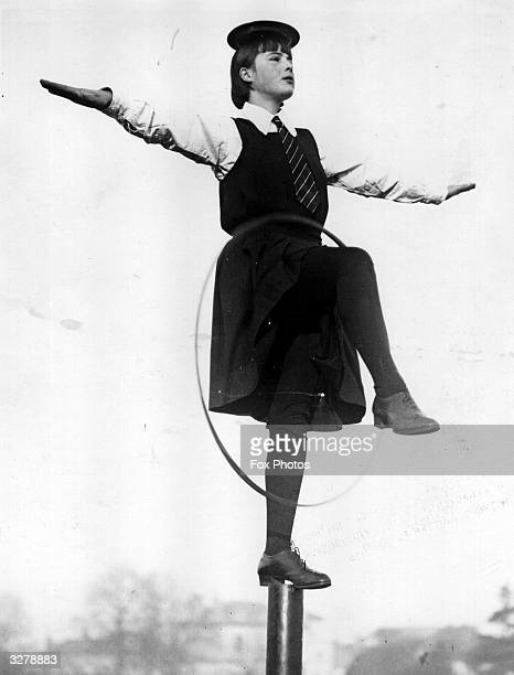 School girl from Pengworn Ladies College, Cheltenham learning tha art of balancing to cultivate good carriage in walking by balancing a plate on her...