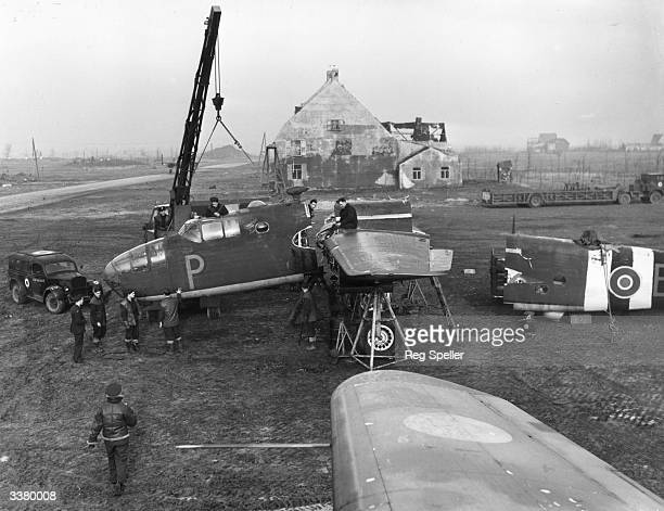 A B25 Mitchell of 180 Squadron being repaired In the background is a camouflaged building used by the Germans as a workshop and an RAF 'Queen Mary'...