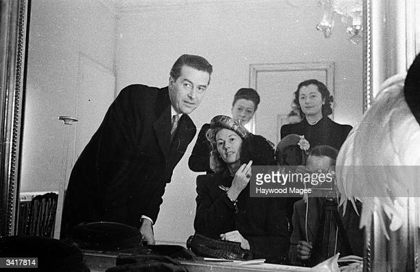 Actor Ray Milland looking in a mirror with his wife as she tries various hats during a shopping trip to Paris Original Publication Picture Post 4274...