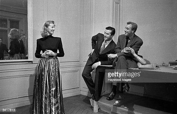 Actor Ray Milland sits with French fashion designer Jacques Fath while Mrs Milland tries on an evening dress from his collection Original Publication...