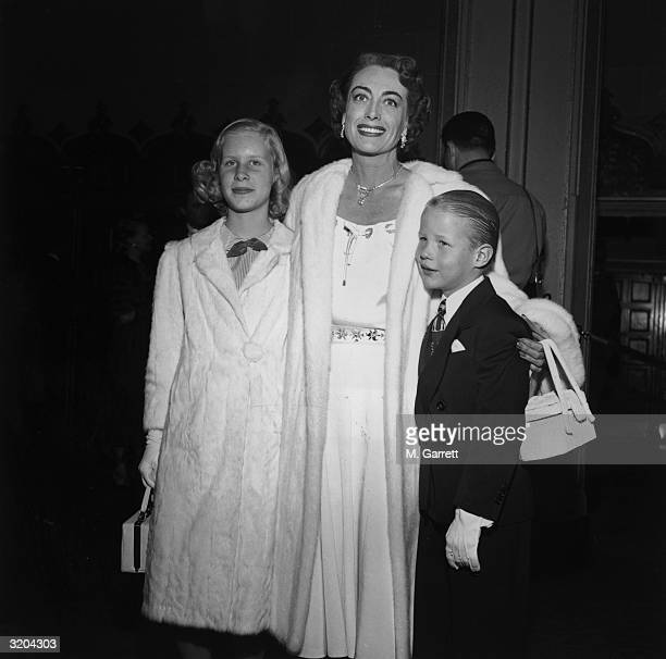 EXCLUSIVE American actor Joan Crawford smiles as she poses with her daughter Christina and her son Christopher at the premiere of director Vincent...