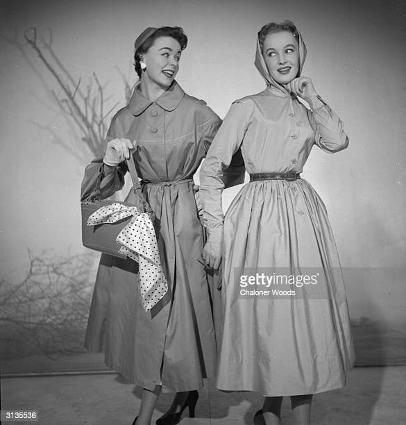 Two women modelling raincoats and hats