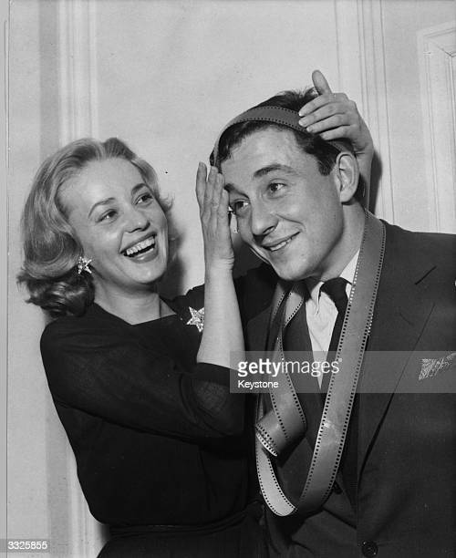 French actress Jeanne Moreau places a roll of film around French director Louis Malle's head after he won the annual Prix Delluc for his first...