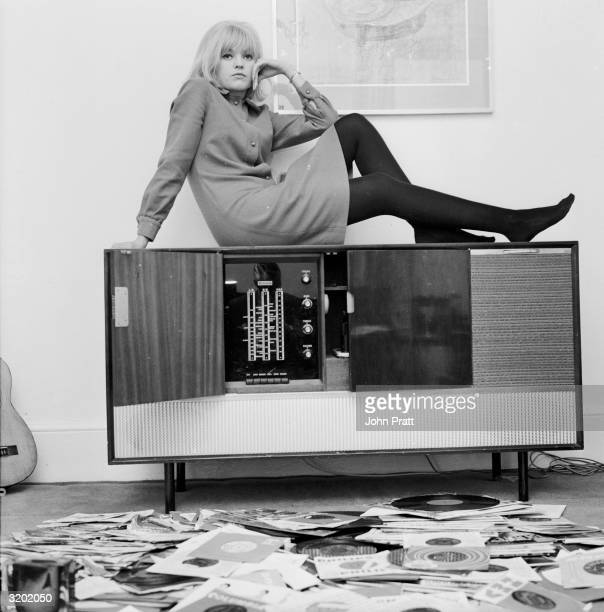 Disc jockey and presenter of 'That's For Me' on television, Anne Nightingale reclines on her stereogram at her home in Brighton.