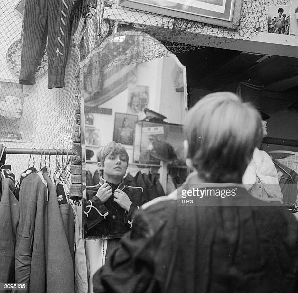 Sixteenyearold Susan James tries on a secondhand navy jacket at the 'I Was Lord Kitchener's Valet' boutique in Portobello Road west London