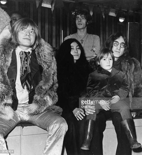 From l to r Rolling Stone Brian Jones with Yoko Ono John Lennon of the Beatles and the latter's son Julian at a Wembley studio Standing behind them...