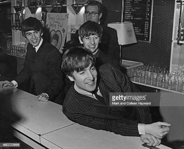 George Harrison Ringo Starr and John Lennon from The Beatles posed behind the bar at the Wimbledon Palais in South London on 14th December 1963...