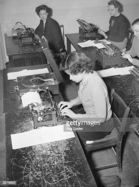 Miss Jean Oliver a trainee typist at the Ministry of Labour training centre at Perivale Middlesex learning to type by using a gramophone record to...
