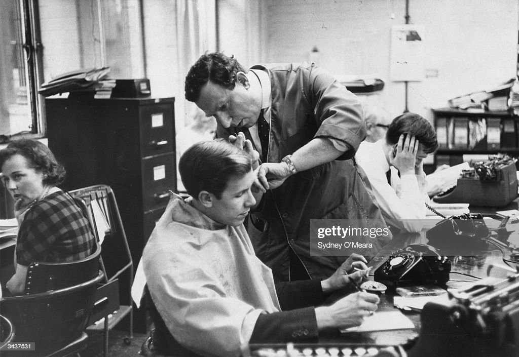 Montague Clifford,a mobile barber, cutting a young man's hair while he smokes a cigarette and writes a letter at his desk in a busy office.
