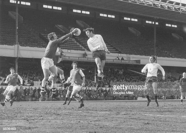 Arsenal goalie Bennett leaps high to grab the ball away from the head of Tottenham Hotspur striker Jimmy Greaves following a corner kick On the right...