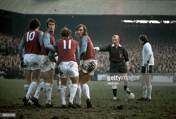 West Ham United players Geoff Hurst and Billy Bonds turn to look behind them as they make a wall for a free kick during the fourth round FA Cup...