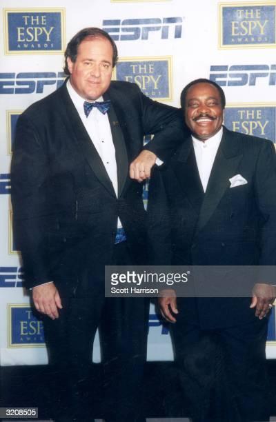 Football commentator Chris Berman rests his shoulder on ESPN baseball analyst and National Baseball Hall of Famer Joe Morgan's shoulder at the eighth...