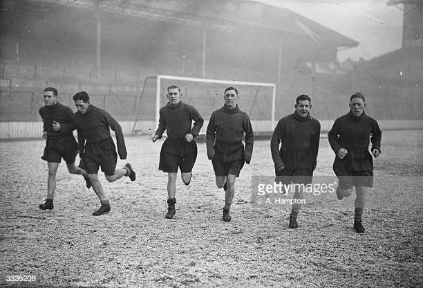 Tottenham Hotspur players train on a frosty pitch in their new rubber boots