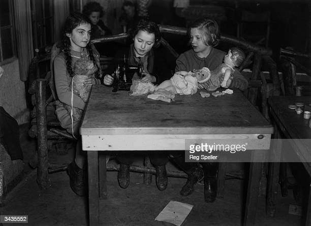 Three young Jewish refugee girls playing with dolls at their camp at Dovercourt Bay near Harwich