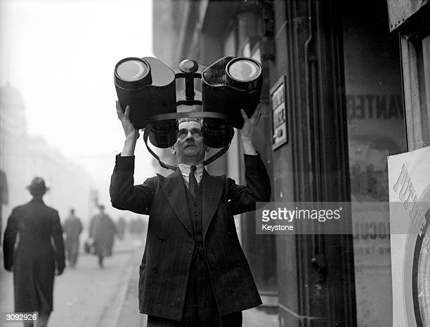 An official at a ministry depot trying out one of the more unusual pieces received after a government plea for donations of binoculars