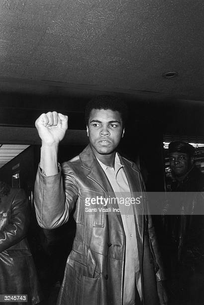 American boxer Muhammad Ali, formerly Cassius Clay, giving a Black Power salute before entering Madison Square Garden to fight Argentinian boxer...