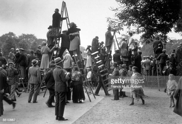 Enthusiastic Parisians using steps and ladders to get a view of a Bastille Day procession