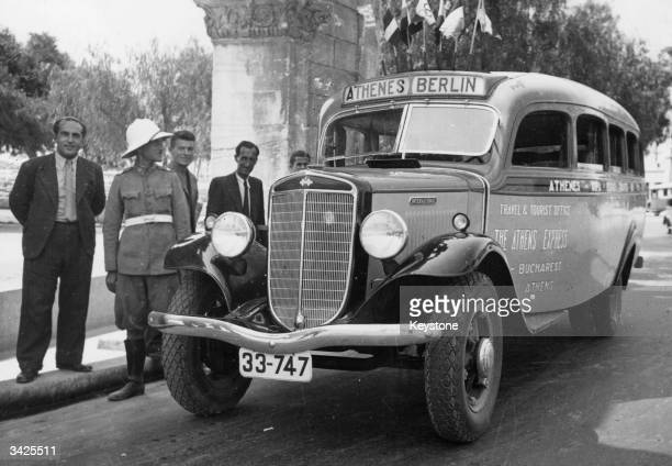 A bus bearing the sign 'Athenes / Berlin' with some members of the German Olympic team standing by