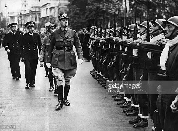 French General and statesman Charles de Gaulle inspecting French troops in Whitehall London at the Quatorze Juillet ceremony celebrating the fall of...
