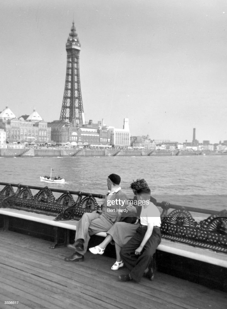 A family sitting on Blackpool Pier to admire the famous sight of Blackpool Tower. Original Publication: Picture Post - 5358 - Bert Hardy's Box Camera - pub. 1951