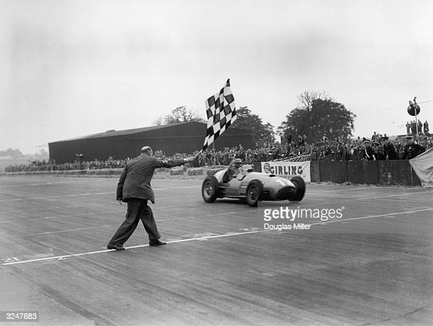 Froilan Gonzalez takes the winning flag in his Ferrari 375 at the British Grand Prix at Silverstone.