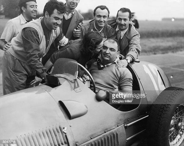 Jose Frolien Gonzalez is kissed by his wife after winning the British Grand Prix at Silverstone in his Ferrari 375