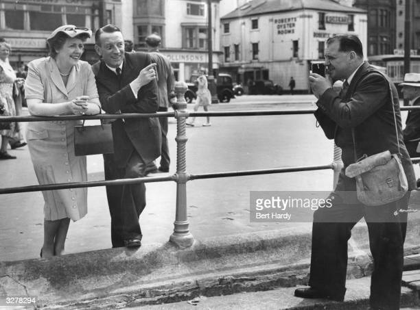 Picture Post photographer Bert Hardy photographs radio personality Wilfred Pickles and his wife with a cheap box camera as they enjoy a stroll along...