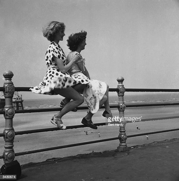 Two young women enjoy a summer day on Blackpool promenade as they sit on the railings with the wind billowing their skirts They are former Tiller...