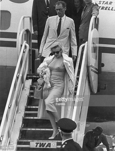 Fulllength image of American actor Marilyn Monroe and her husband American playwright Arthur Miller descend an airplane ramp after arriving at London...