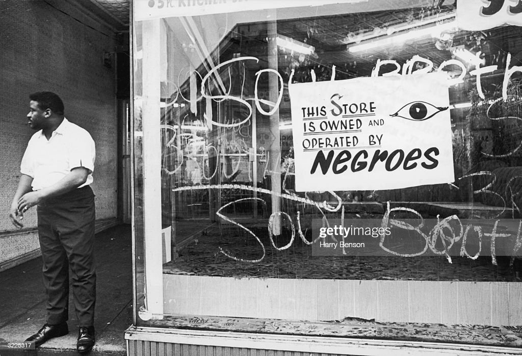An African-American storekeeper stands outside his shop, which has a sign reading, 'This store is owned and operated by Negroes,' during the race riots in Newark, New Jersey. There is writing scrawled on the window, reading 'Soul Brother.'