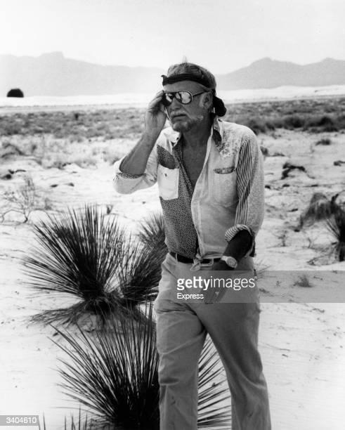 American film director Sam Peckinpah walking across a salt marsh in sweltering heat