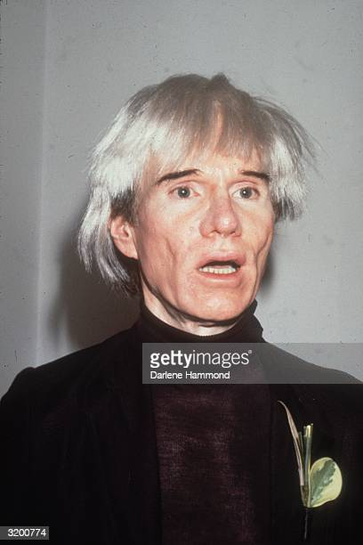 American artist Andy Warhol talking wearing a black jacket and a turtleneck with a leaf brooch