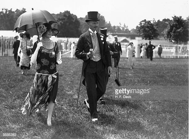 Captain and Mrs Ambrose Goddard stroll around the enclosure on the opening day of Royal Ascot