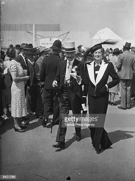 Racegoers at Ascot in formal clothing grey topper and tails for the man and a striking long skirted suit for the woman worn with a feather trimmed hat