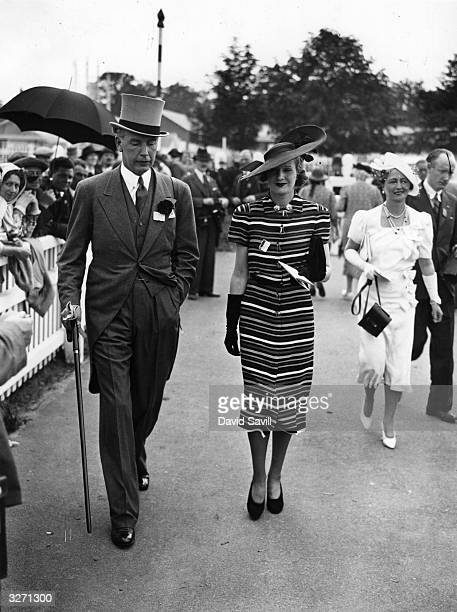 Spectators at Royal Ascot The man is wearing a traditional morning dress and the woman a striking dress and widebrimmed hat