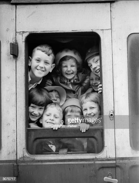 A group of wartime evacuees at the window of a train carriage before their departure from London to the comparative safety of the countryside