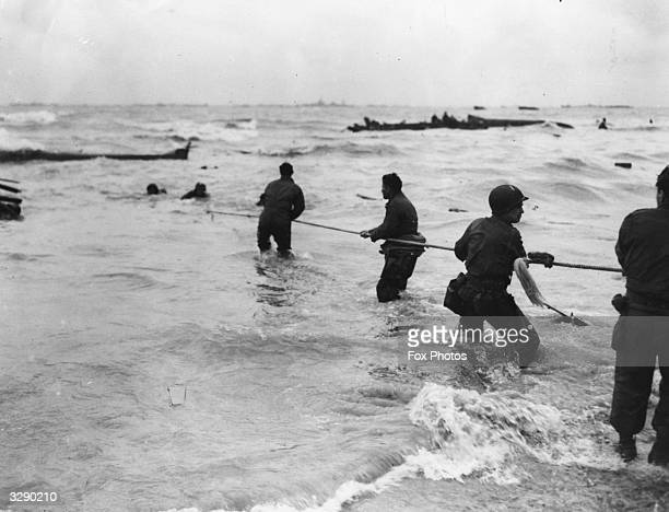 American soldiers waist deep in water with a lifeline helping to rescue other Americans from a sinking landing craft which was hit by enemy fire...