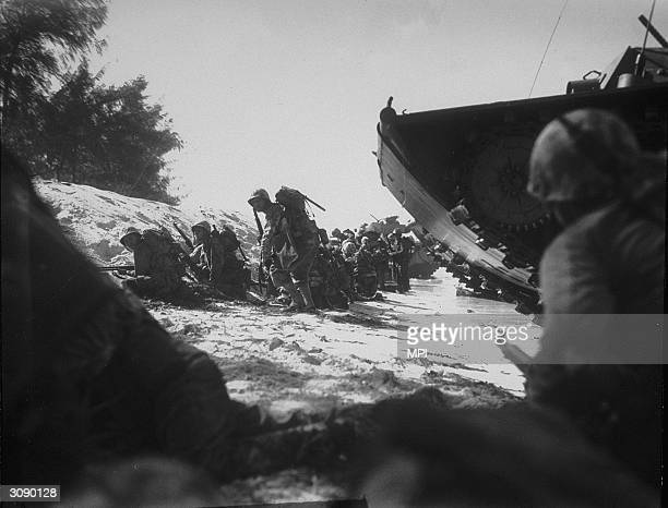 American troops crouch on a sloping beach under the shelter of their landing craft