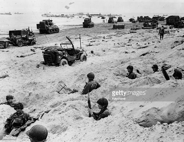 Members of the Allied Invasion Force keeping watch from fox holes dug in the beachhead while fresh troops and equipment continue to be landed