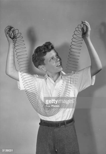 A boy holds up a 'slinky' Made of a coil of wire which if straight would be 75 feet long a 'slinky' will 'climb' down a flight of stairs when coiled...
