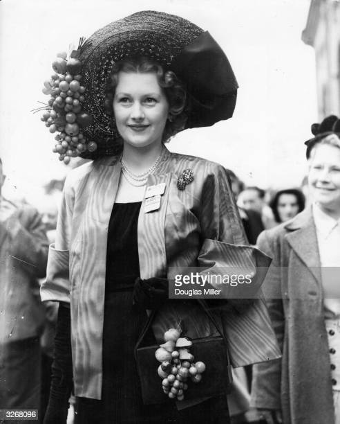 Mrs Gerald Legge who is the daughter of novelist Barbara Cartland sporting a large cherry trimmed hat and bag on the second day of the Ascot meeting
